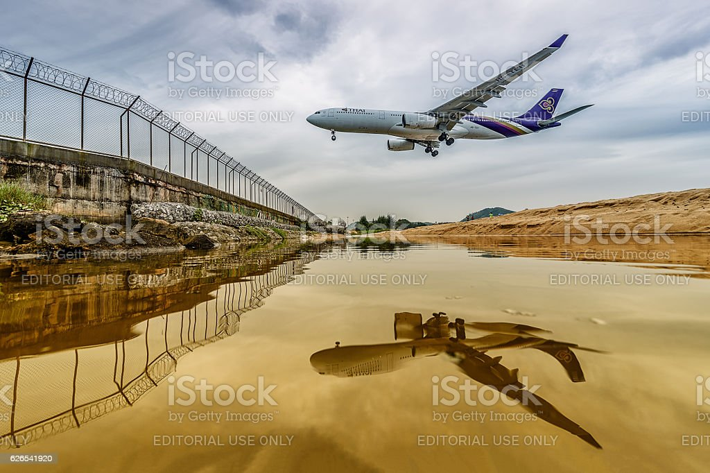 Thai  airways airplane  landing  at phuket airport with reflect - Photo