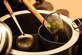 Thai Asian Street Food on rowing boat, fresh white rice Noodle Blanched in Noodle strainer basket with wood handle and warm aluminum stock boiler pot with smoke in soft warm sunset light background