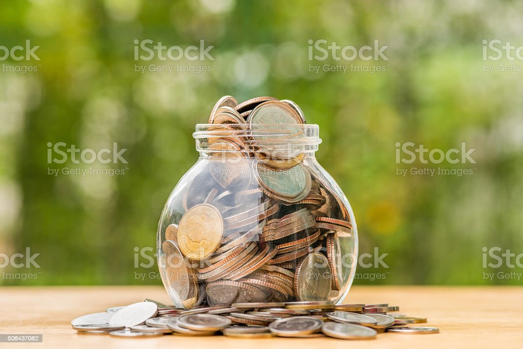 Thai baht coins spilling out of money jar stock photo