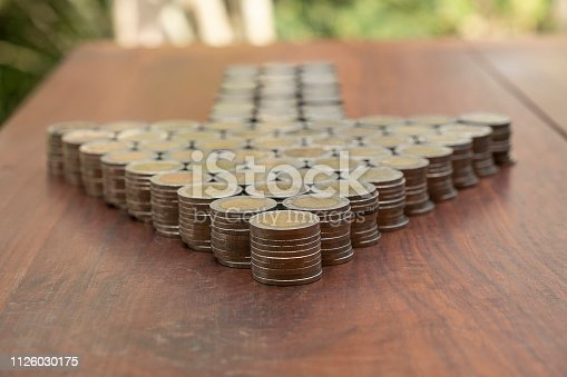 istock Thai Baht lots coin Arranged in arrow shape on with blurred background texture, Money stack for business planning investment and saving concept 1126030175