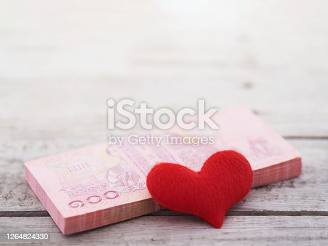 Close up pile of Thai banknotes 100 baht and heart shape on wooden table background. Love shopping concept.