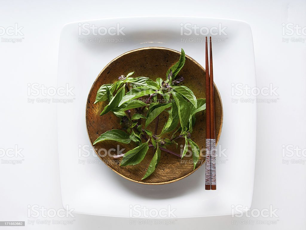 Thai Basil in Gold Bowl With Chopsticks stock photo