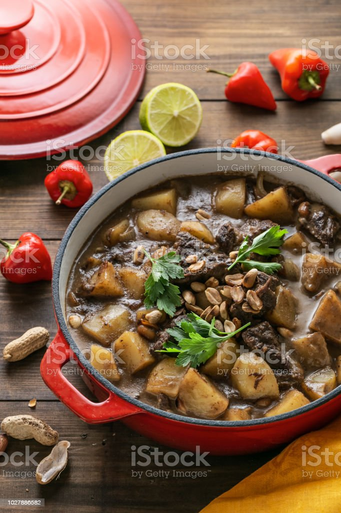 Thai Beef Massaman Curry served in big red pot, top view stock photo