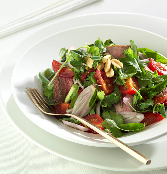 Thai beef salad in a white bowl stock photo