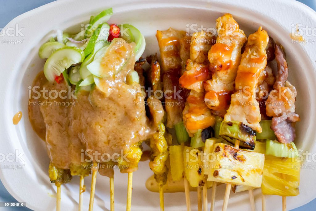 Thai beef satay on paper plate with the cucumber and peanut sauce royalty-free stock photo