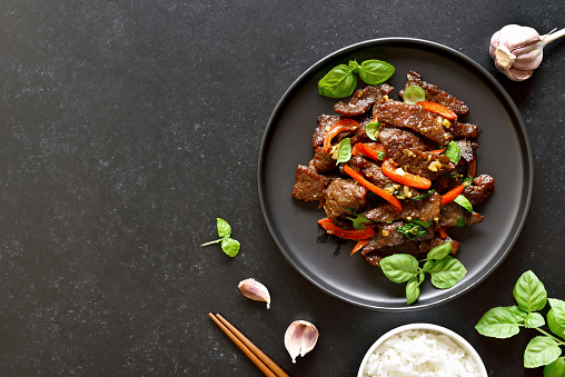 Thai beef stir-fry with pepper and basil on plate on a dark stone background with copy space. Top view, flat lay