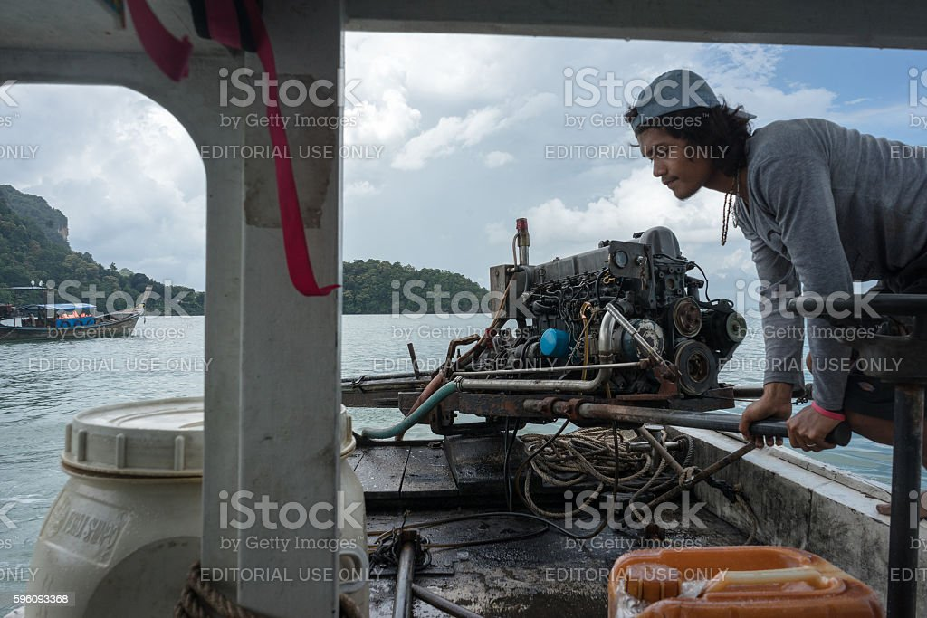 Thai boat driver sailing long tail boat with engine royalty-free stock photo