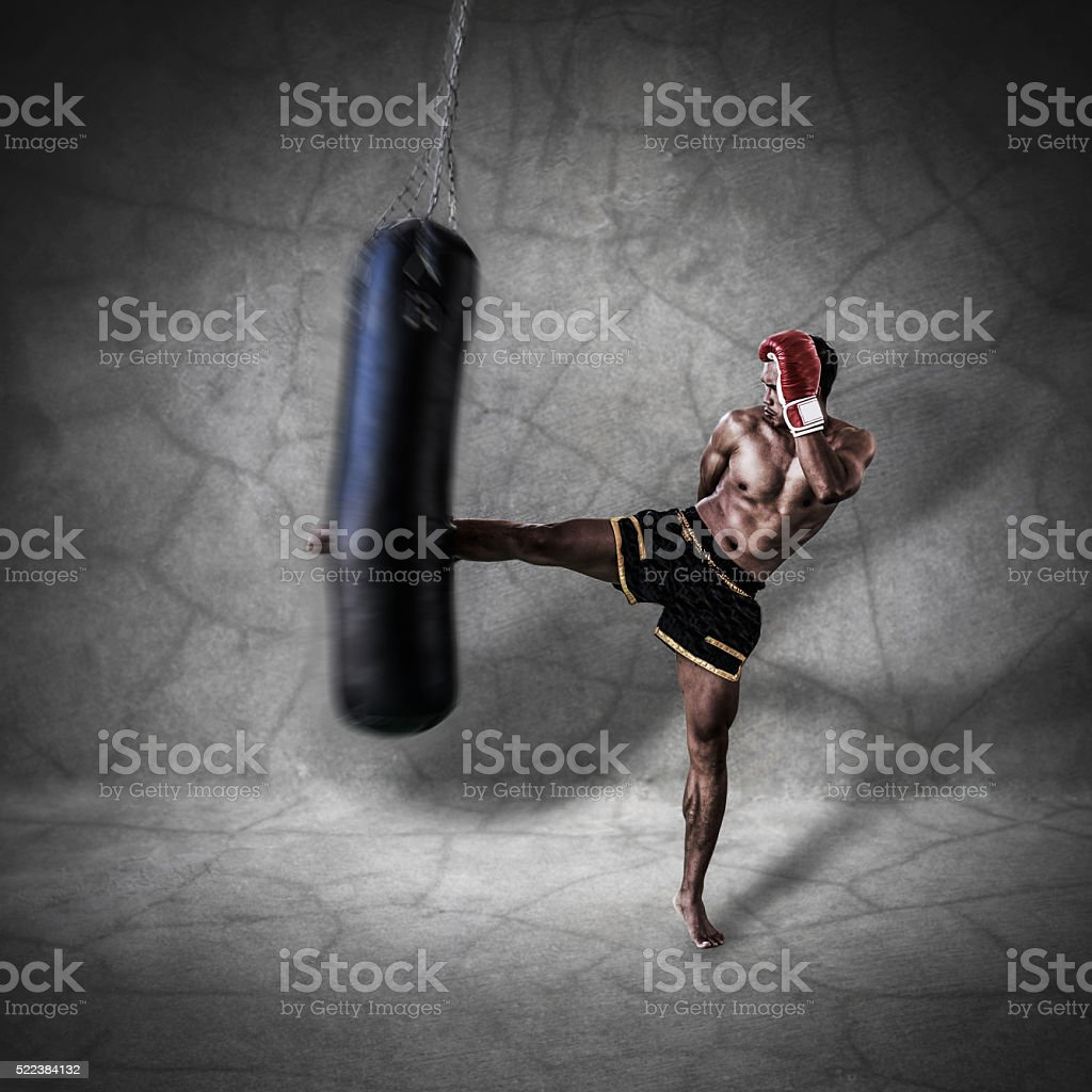 thai boxer character is kicking the sand bag stock photo