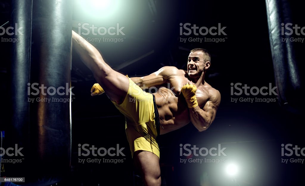 Thai boxer punch kick by punching bag, black bacground, horizontal photo stock photo