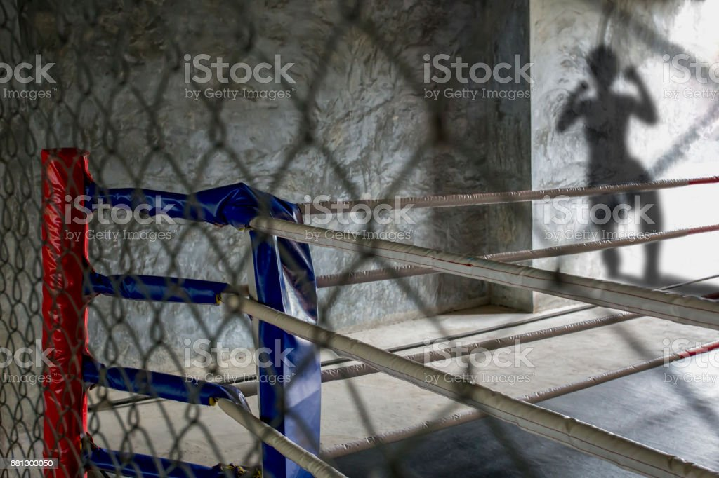 A Thai boxing ring while Thai boxer is coming to fight Muay Thai can see by his shadow. stock photo