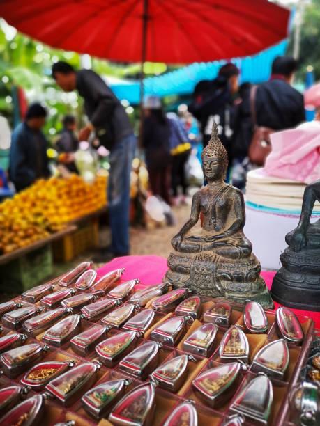 thai buddha amulette und buddha-figuren zum verkauf an einen lokalen allgemeinen nördlichen thai-markt in chiang mai province, menschen sehen unscharf im hintergrund einkauf frisches obst. - buddha figuren kaufen stock-fotos und bilder