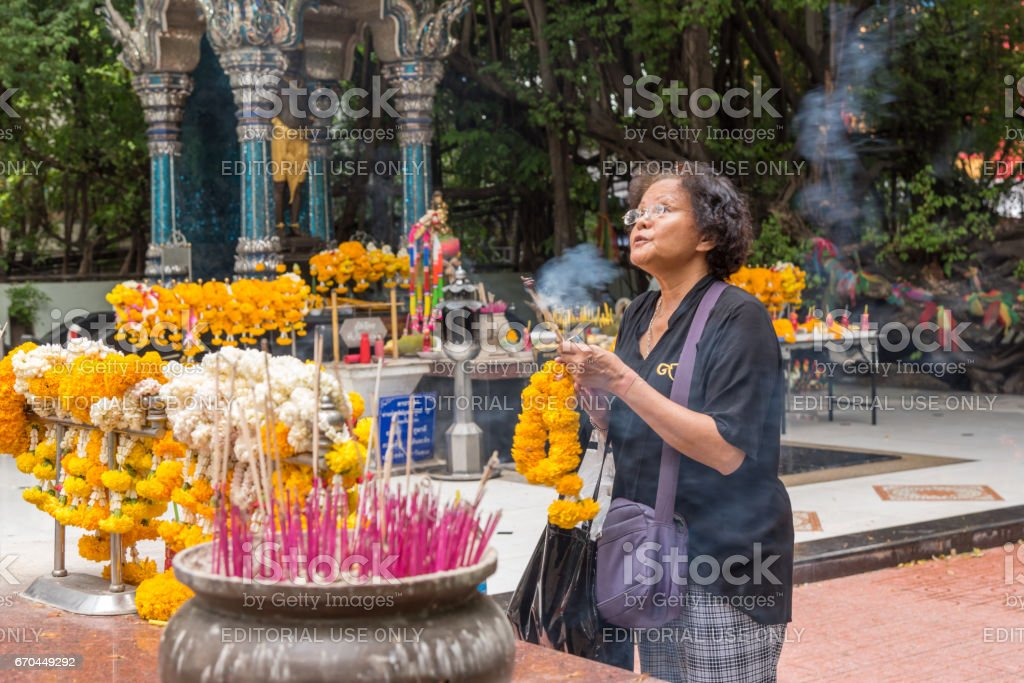 Thai buddhism people in buddhist pray for benefaction worship by incense and garland to Buddha or spirit-house at shrine or Thai temple (Wat Thai) stock photo