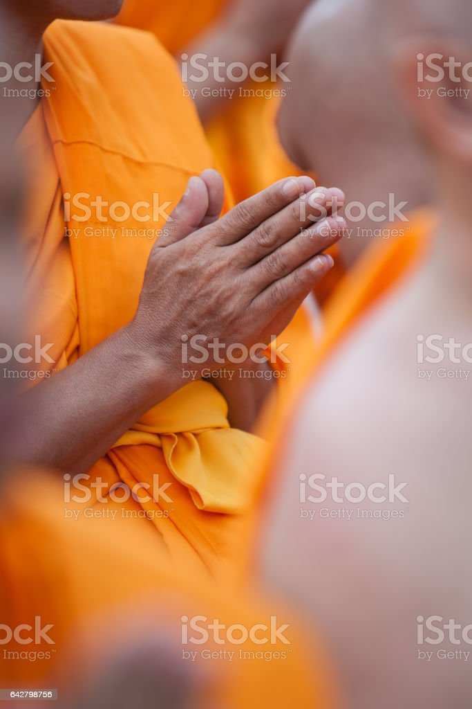 Thai Buddhist monks wai-ing in respect of the Lord Buddha at a Buddhist temple in Thailand. Selective focus on the hands in the foreground. stock photo