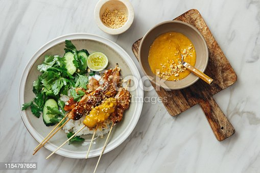 Thai chicken satay with peanut sauce on marble background