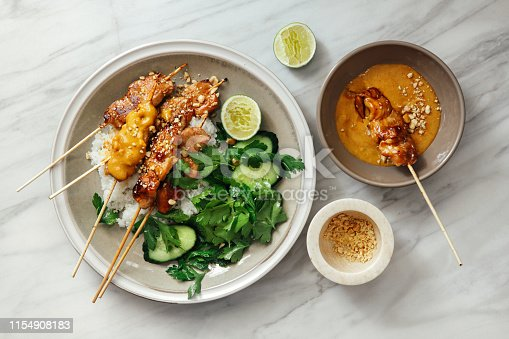 Thai chicken satay with peanut sauce on marble background
