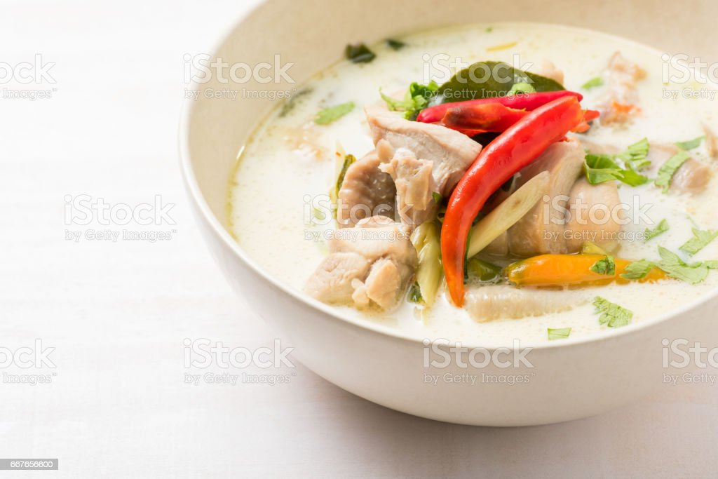 Thai chicken soup in coconut milk on white wooden table stock photo