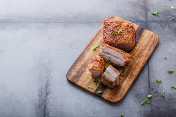 Thai crispy skin pork belly on wooden board, copy space stock photo