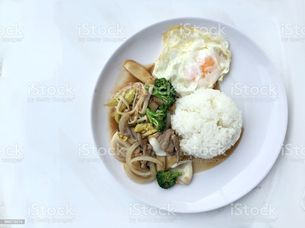 Thai cuisine. Stir-fried colorful vegetables, onion, broccoli, mushroom with meat in white plate with rice and fried egg on white background. Thai style food in fast street restaurant. royalty-free stock photo