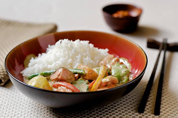 thai-curry mit fisch, gemüse und reis in asiatisches ambiente - curry reis stock-fotos und bilder