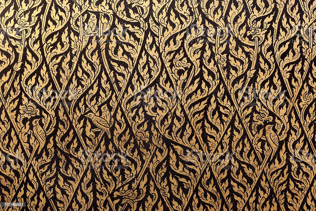 Thai decorative gilt lacquer motif on an antique cabinet. stock photo