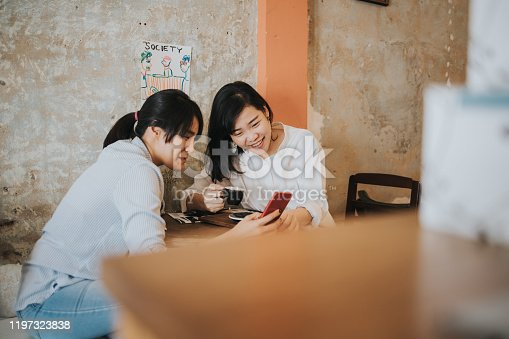 laughing, smiling, togetherness, enjoyment, lifestyles, friendship, coffee shop, women using phone, photographing, hot drink, drinking, resting, Bangkok, Thailand