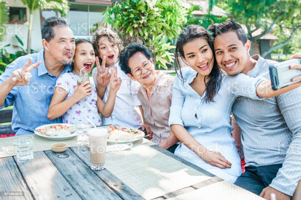 Thai family - grandpa, grandma, mom, dad, daughter and son - having lunch  at a terrace. Taking selfies and having fun - Stock image .