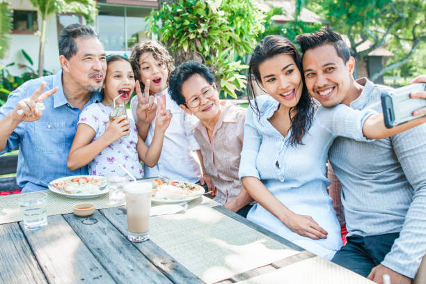 Thai family - grandpa, grandma, mom, dad, daughter and son - having lunch at a terrace. Taking selfies and having fun stock photo