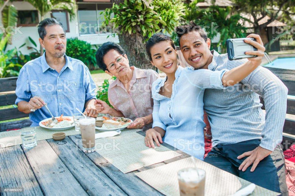 Thai family - grandpa, grandma, mom, dad - having lunch at a terrace. Taking selfies and having fun stock photo
