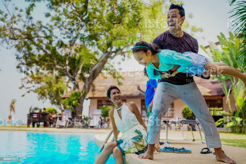Thai family having fun playing near the swimmimg pool. Wet clothes stock photo