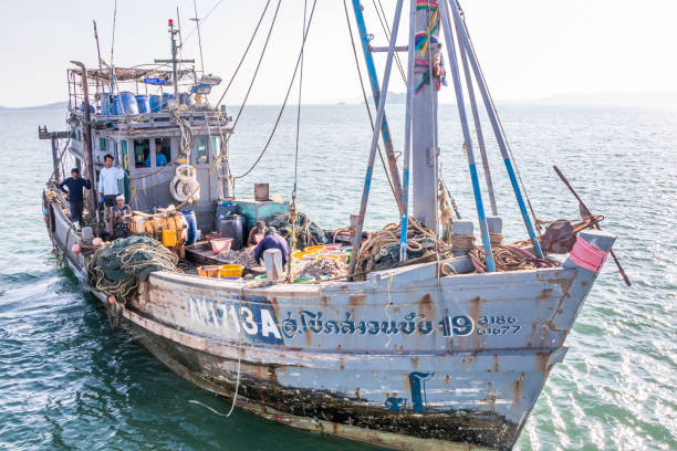 Thailändisches Fischerboot mit burmesischem Besatzungsmitglied. – Foto