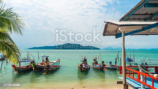 Ko Samui, Thailand - January 2, 2020: Authentic Thai fishing boats anchored at Thong Krut beach near French bakery on a bright day