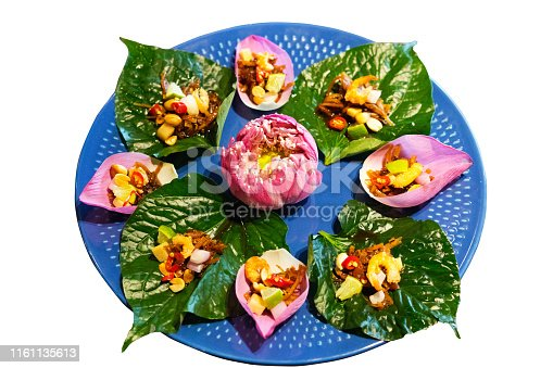 Thai food on spinach leafs with pink lotus flower in center