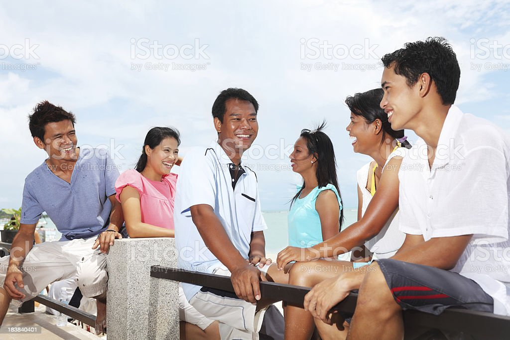 Thai friends communicate on the beach. royalty-free stock photo