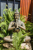 Sand stone statue of young novice was meditating until he was asleep for garden decoration.