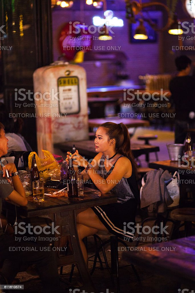 Thai girl with e-cigarette and drinks stock photo