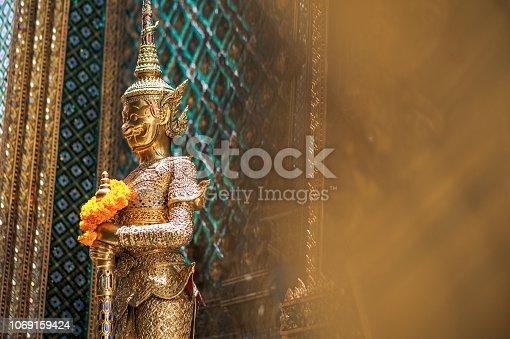Thai golden statue in standing position outside of Wat Pho, Bangkok