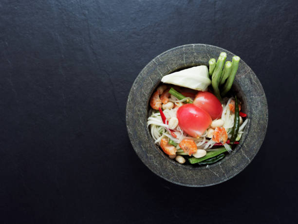 Thai green papaya salad Som tam in granite mortar on dark background stock photo
