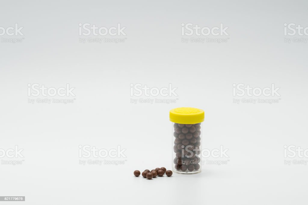 Thai herbal medicine in plastic bottle with modern design and many pills spread on a white background, bolus stock photo