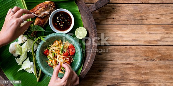 Thai lady eating traditionally with her hands, fresh world famous Som Tam (papaya salad) with BBQ chicken, sticky rice and raw salad vegetables on an old wooden table background.  Good copy space to the right of the image.