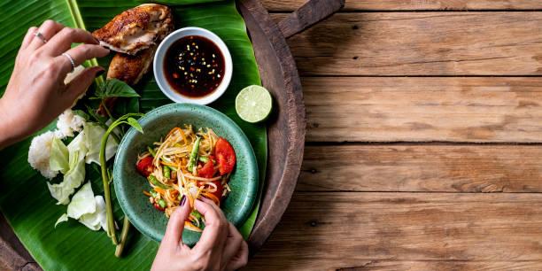 thaise dame eten traditioneel met haar handen, verse wereldberoemde som tam (papaya salade) met bbq-kip, kleverige rijst en rauwe salade groenten op een oude houten tafel achtergrond. - thai food stockfoto's en -beelden