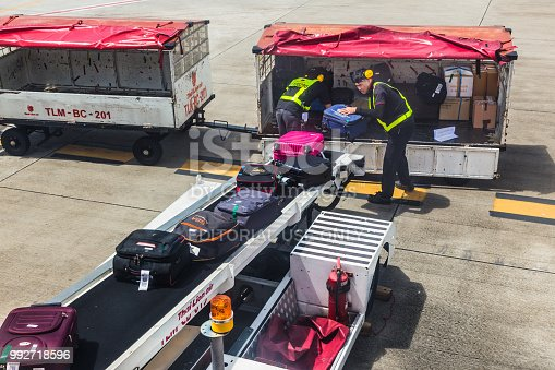 CHIANG MAI, THAILAND - 28 June 2018 - Thai Lion Air ground staff load passenger luggages on the airplane through the conveyor on June 28, 2018 at Chiang Mai International Airport, Thailand