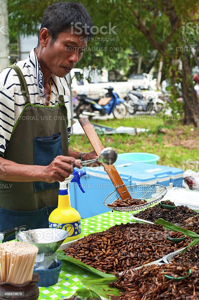 Thai man selling fried insects at market royalty-free stock photo
