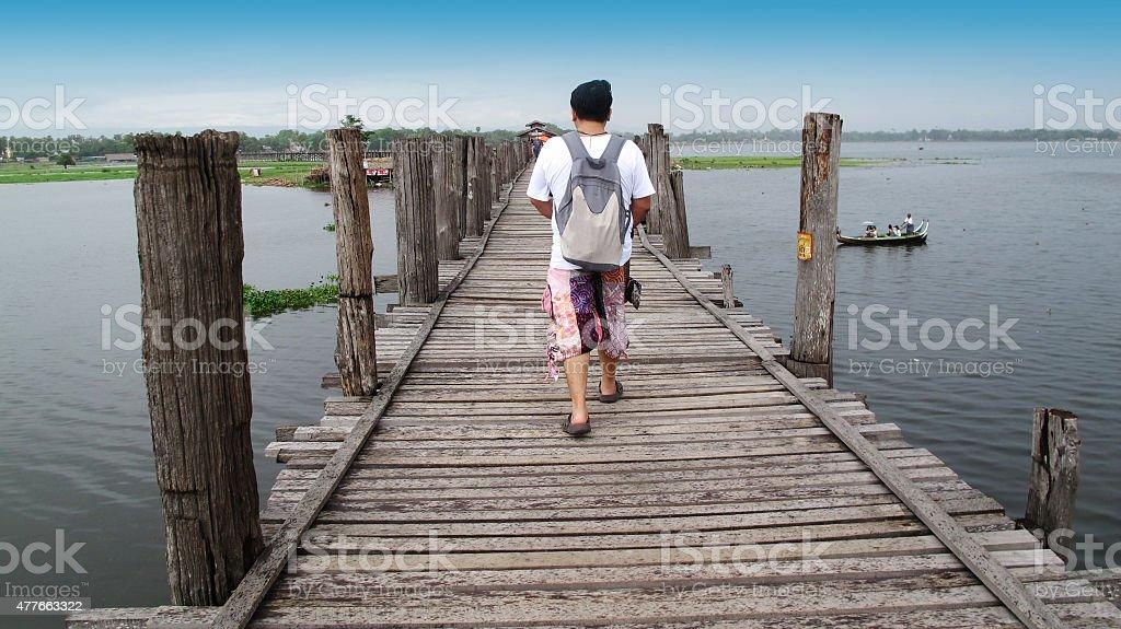 Thai man travel and walking at U Bein Bridge stock photo
