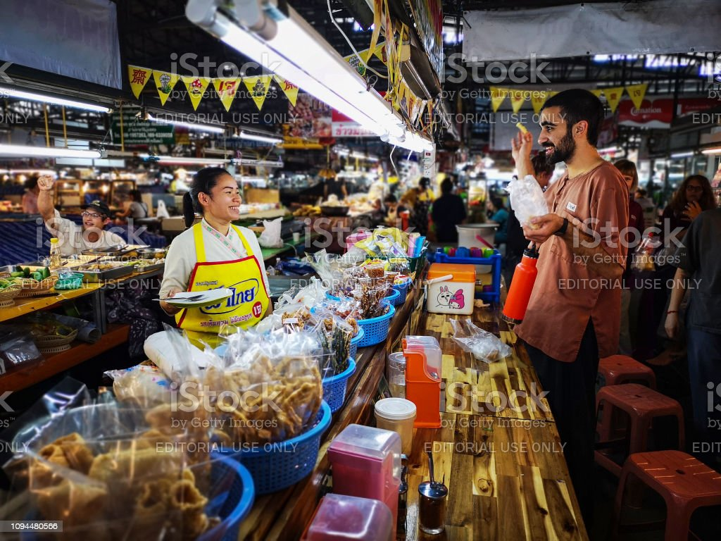 Thai market vendor selling Thai food to a Caucasian tourist at a...