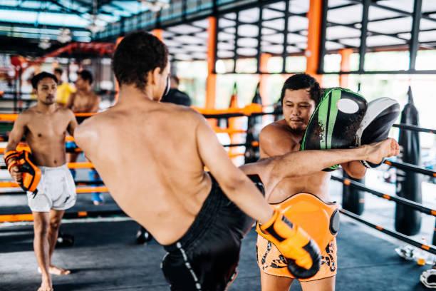 thai martial arts-trainerinnen, die mit internationalen auszubildenden in muay thai camp - wortarten bestimmen übungen stock-fotos und bilder