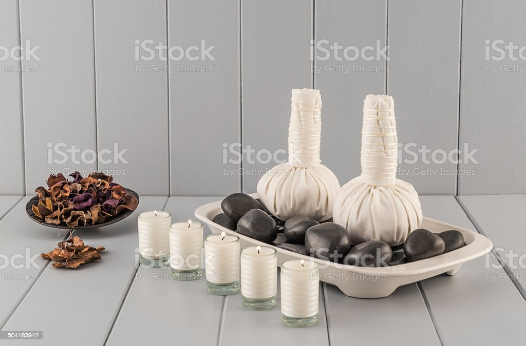 Thai Massage Balls on Hot Stones with Herbs and Candles stock photo