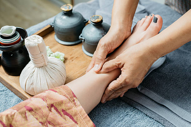 thai massage series : foot and leg massage - thai massage stock photos and pictures