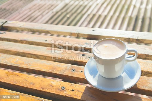1135319558 istock photo Thai milk tea in white ceramic cup put on the wooden table with beautiful mountain landscpe scenery and sun light in the morning. 882012766