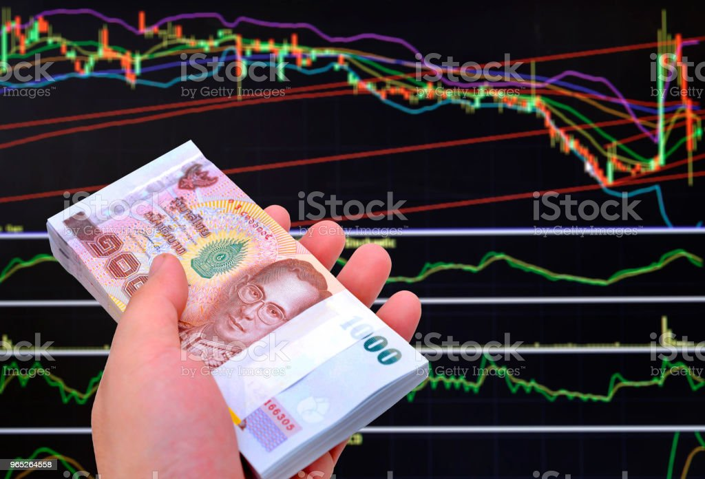 Thai money 1000 baht banknotes on stock chart background. royalty-free stock photo