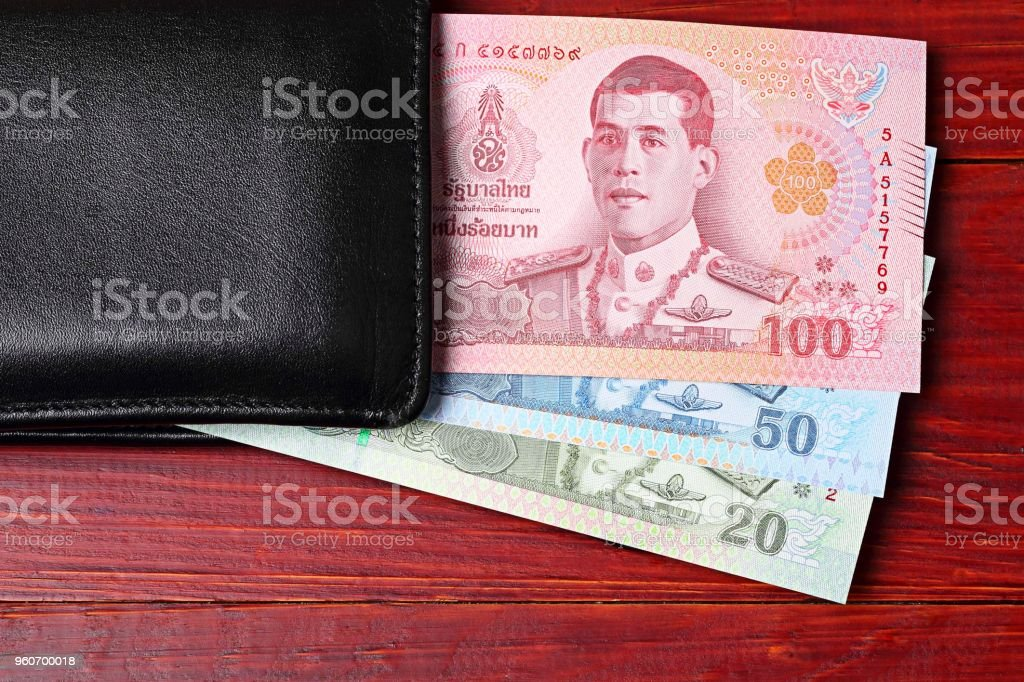 Thai money in the black wallet on a wooden background